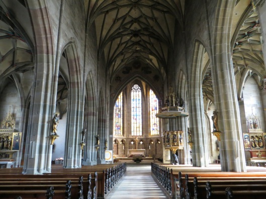 Church of the Holy Cross, Rottweil, Germany.  A carved crucifix attributed to Veit Stoss is visible at the center of the photograph, behind the main altar.