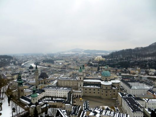 View of Salzburg from Festung Hohensalzburg.  Salzburg Cathedral, with green dome, is visible in the foreground, to the right.